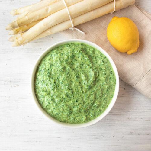 Schüssel mit veganer grüner Soße, daneben weißer Spargel und eine Zitrone